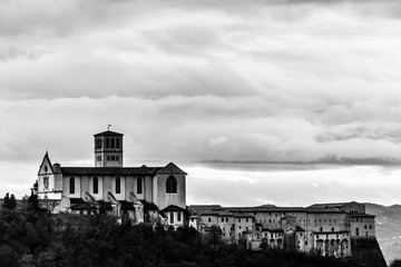Beautiful view of St.Francis church in Assisi town (Umbria, Italy) from an unusual place, with moody clouds in the sky