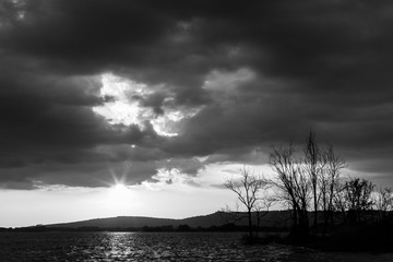 Beautiful wide angle view of a lake with an huge sky with clouds, above skeletal trees