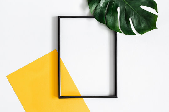 Summer composition. Tropical palm leaves, yellow paper blank, photo frame on pastel gray background. Summer concept. Flat lay, top view, copy space