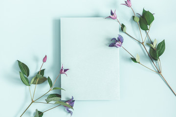 Flowers composition. Purple flowers, paper blank on pastel blue background. Spring concept. Flat lay, top view, copy space