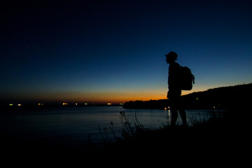 a man standing on the black sea and looking into the distance at the sunset