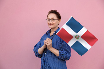Dominican Republic flag. Woman holding Dominican Republic flag. Nice portrait of middle aged lady 40 50 years old holding a large flag over pink wall background on the street outdoors.