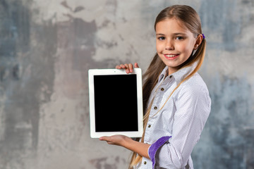 Smiling blonde girl holding ipad in her hands and looking at the camera. - Vertical image mockup