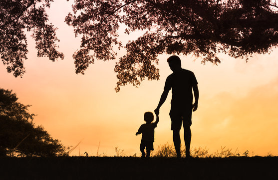 father and son holding hands walking in the park