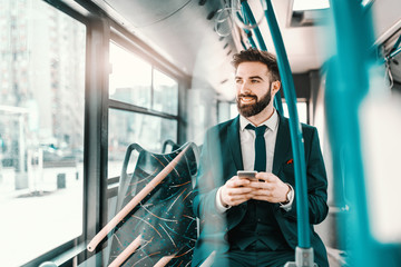 Smiling bearded Caucasian businessman in formal wear sitting in public transport and using smart phone.