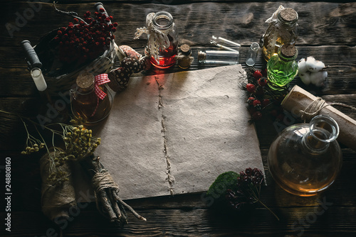 Ancient recipe scroll book and various dry herbs on a table