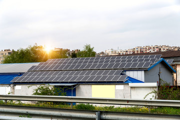 Solar panels, photovoltaics over the roof of an industrial building -  alternative electricity source. Concept of sustainable resources