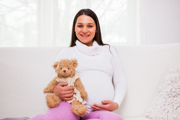 Happy pregnant woman sitting at sofa in home.