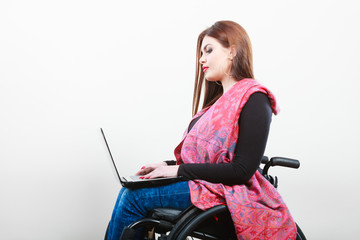 Young girl on wheelchair surfing web.