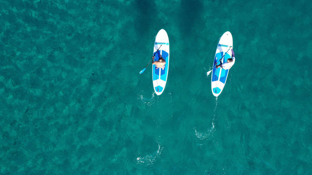 Aerial drone bird's eye view of 2 men exercising sup board in turquoise tropical clear waters