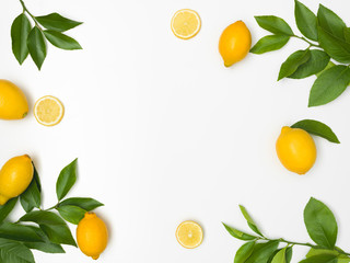 fresh, juicy, yellow lemons with green twigs lie on a white background