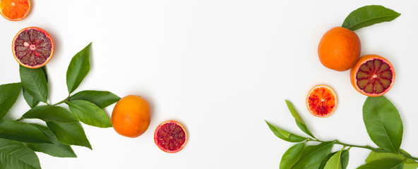 fresh, juicy, red blood oranges with green twigs lie on a white background