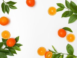 fresh, juicy oranges with green twigs lie on a white background