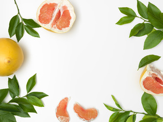 fresh, juicy pomelo with green twigs lying on a white background