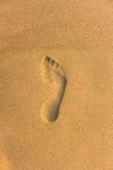 imprint of the bare right foot on the yellow sand