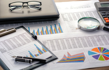 Financial documents - graphics, statistics, drawings, keyboard, laptop, magnifying glass in the office. Business, science, long hours of work.