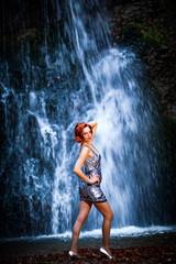 Porträt einer rothaarigen Frau im silbernen Minikleid, vor einem Wasserfall