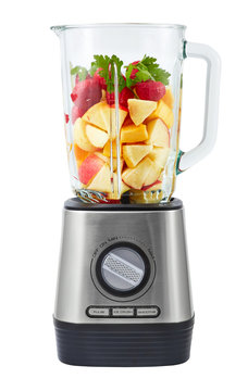 Stationary blender filled with slices of apples, pumpkins, strawberries for making smoothie.