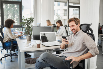 CEO with smile sitting in his chair and using smart phone. Office interior, in background employees working.
