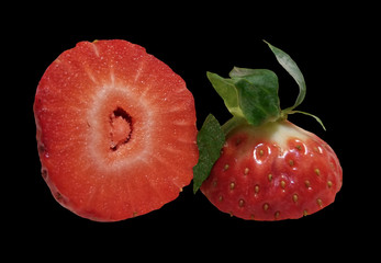 Single closeup of strawberry cut in half on a black background
