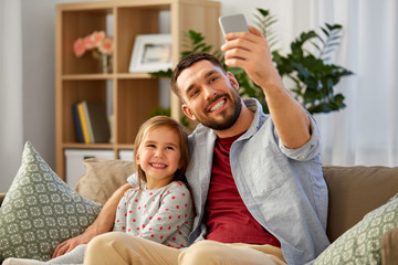 people, family and technology concept - happy father and little daughter taking selfie by smartphone sitting on sofa at home
