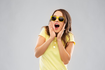 summer, accessory and people concept - amazed young woman or teenage girl in yellow t-shirt and sunglasses over grey background