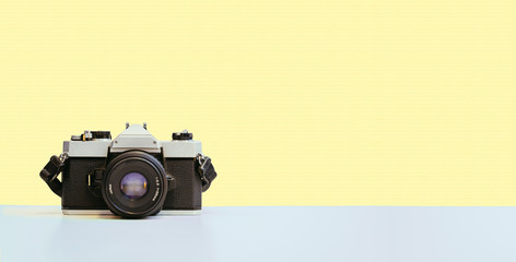 Vintage photography camera on yellow colored background, retro