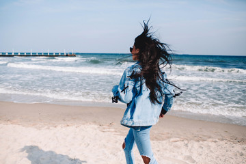 Freedom woman in free happiness bliss on beach. Smiling happy multicultural female model in jeans coat enjoying serene ocean nature during travel holidays vacation outdoors, running on the beach.