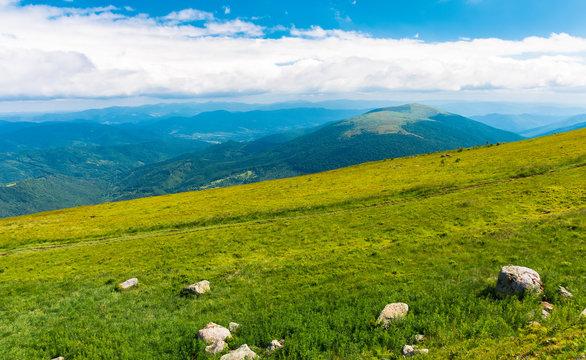 summer mountain scenery. rocks on the grassy meadow. distant ridge beneath a cloudy sky. beautiful vivid landscape of carpathian mountain.