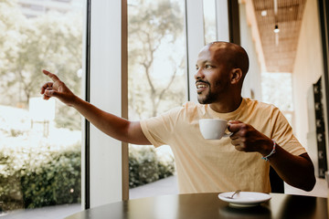 New happy summer day. Young confident African man enjoying his morning coffee and french croissant while sitting at modern urban cafe
