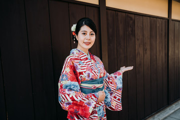 japanese local girl in floral kimono smiling face camera with welcome hand gesture standing on wooden wall in background. lady in traditional dress host telling people to come to visit kyoto japan.