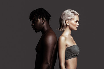 African-American man and white woman standing back to back