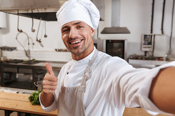 Photo of european male chief in apron taking selfie, while standing at kitchen in restaurant