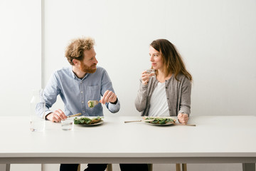 Thirty something European couple sitting down for a avocado sandwich lunch together looking at each other.