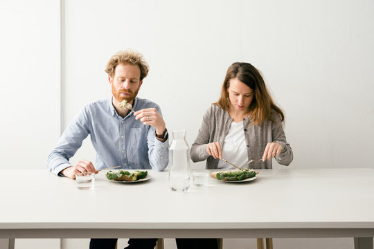 Thirty something European couple sitting down for a avocado sandwich lunch together.