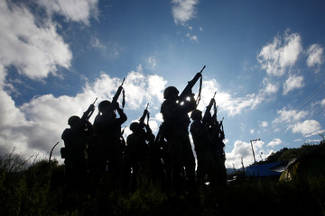 Soldiers unload their weapons at a camp near the area were they found an illegal opium plantation near Pueblo Viejo in the Sierra Madre del Sur in the southern state of Guerrero