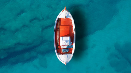 Fototapeta Aerial drone top view photo of beautiful traditional fishing boat docked in clear waters of Koufonisi island port obraz