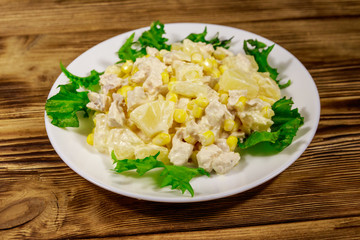 Festive salad with chicken breast, sweet corn, canned pineapple and mayonnaise on wooden table