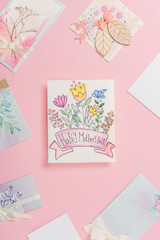happy mothers day greeting card with flowers, and different mothers day postcards arranged around on pink background
