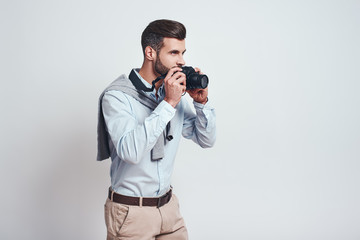 Ready to make a photo. Young attractive man is going to make a photo with camera while standing on a grey background