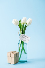 gift box and bouquet of white tulips with happy mothers day greeting label on blue background