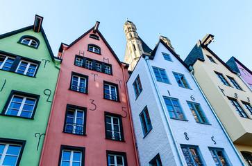 Eine Reihe bunter  Häuser am Rheinufer vor Groß St.Martin Kirche in Köln