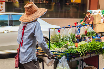Bangkok, Thailand - March 2, 2017: A vegetable vendor pushing a cart filled with local vegetables for sale in the streets of Bangkok, Thailand.