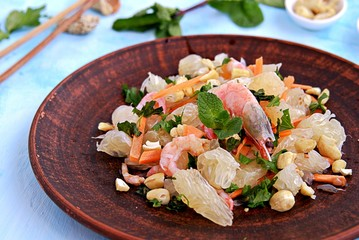 Refreshing salad with pomelo, shrimps, carrots and cashew nuts on a light blue background. Asian cuisine.