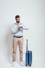 Time to go! Full length of young and stylish bearded man with a luggage checking time on his watch. Travel concept