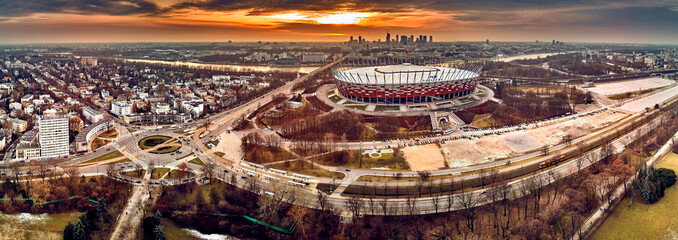 WARSAW, POLAND - FEBRUARY 10, 2019: Beautiful sunset panoramic aerial drone view to panorama of Warsaw modern City with skyscraper and The PGE Narodowy National Stadium (Polish: Stadion Narodowy) Fototapete