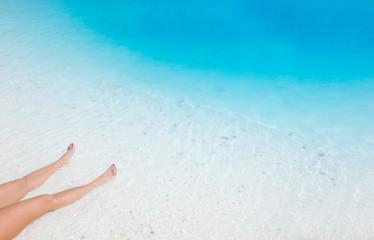 Woman feet on marble beach