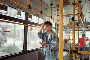 handsome young man in a blue denim jacket using smartphone in bus
