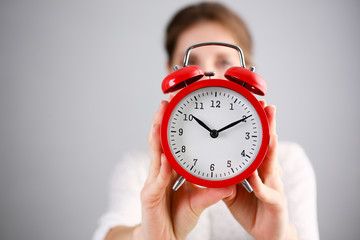 Adult smiling caucasian woman hold red alarm clock on gray background.
