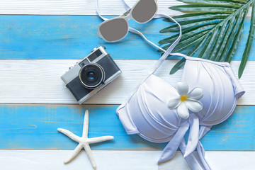 Summer  accessories, white bikini , camera and sunglasses go to travel in the beach. Tropical sea. Unusual top view. Travel and Summertime Concept.